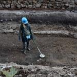 Iskanje izgubljenih predmetov na najstarejši cesti, ki je kasneje postala gradbišče (debela bela plast v preseku plasti v ozadju).  Po gradnji so cesto ponovno uredili in jo skozi stoletja večkrat obnovili. Črna plast s kamni predstavlja t.i. temno plast, svetla plast nad njo pa so srednje- in novoveške njivske površine.