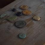 """Slika 9: Nekoč izgubljene sedaj pa ponovno najdene potrebščine za kvalitetno izpeljan """"gambleski večer"""" - nekaj novcev (zaradi inflacije so ga tudi razpolavljal v določenih obdobjih) ter koščeni oziroma stekleni igralni žetoni."""